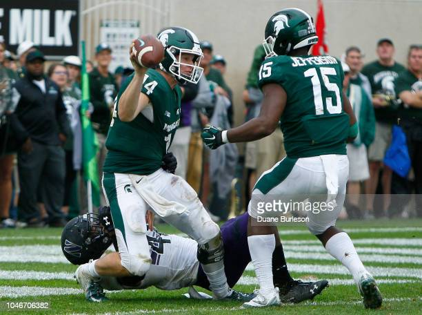 Quarterback Brian Lewerke of the Michigan State Spartans gets a pass off as he is tackled by safety Jared McGee of the Northwestern Wildcats as...