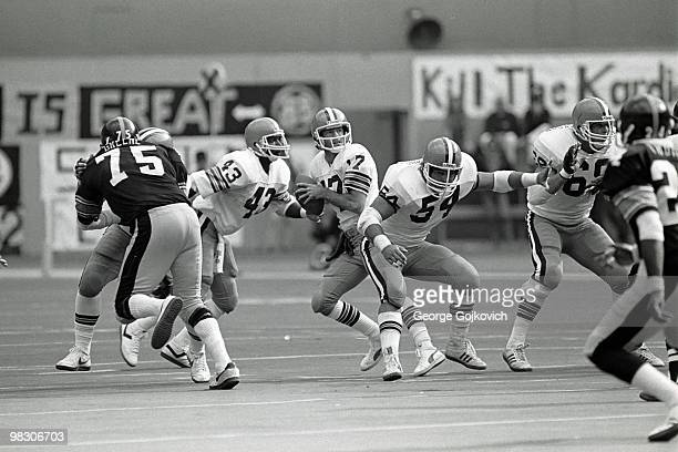 Quarterback Brian Sipe of the Cleveland Browns drops back to pass behind the blocking of running back Mike Pruitt and offensive linemen Tom DeLeone...