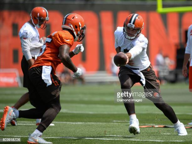 Quarterback Brock Osweiler of the Cleveland Browns hands the ball off to running back George Atkinson III during a training camp practice on July 27...