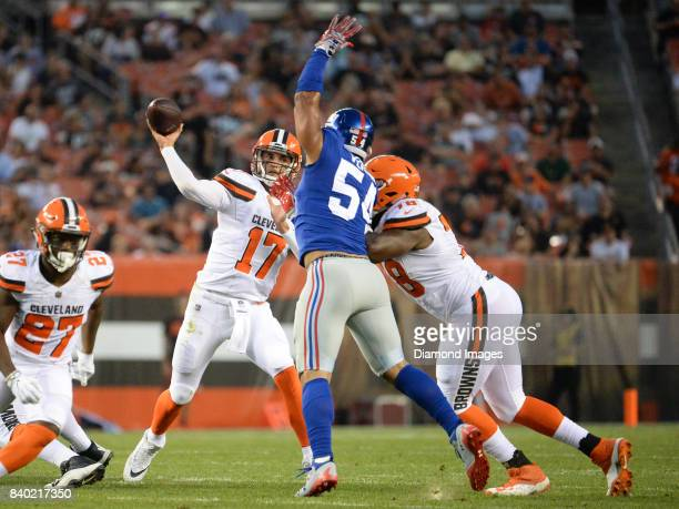 Quarterback Brock Osweiler of the Cleveland Browns throws a pass as defensive end Olivier Vernon of the New York Giants attempts to block the pass in...