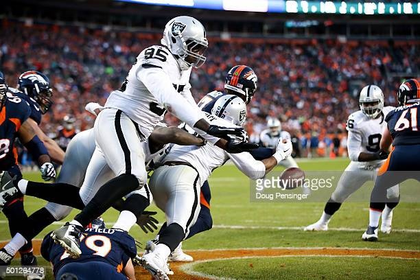Quarterback Brock Osweiler of the Denver Broncos is strip-sacked by defensive end Khalil Mack of the Oakland Raiders as defensive end Benson Mayowa...