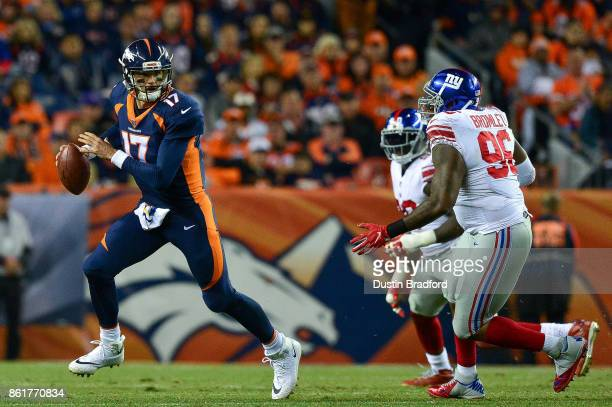 Quarterback Brock Osweiler of the Denver Broncos moves out of the pocket against the New York Giants in the second quarter of a game at Sports...