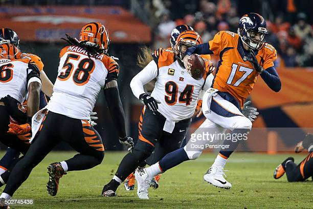 Quarterback Brock Osweiler of the Denver Broncos scrambles as defensive tackle Domata Peko of the Cincinnati Bengals chases him down during a game at...