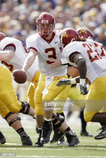 Quarterback Bryan Cupito of the Minnesota Gophers makes a handoff during the game against the Michigan Wolverines at Michigan Stadium on October 8...