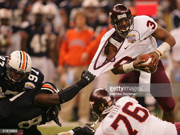 Quarterback Bryan Randall of the Virginia Tech Hokies is grabbed by Jay Ratliff of the Auburn Tigers during the Nokia Sugar Bowl on January 3 2005 at...