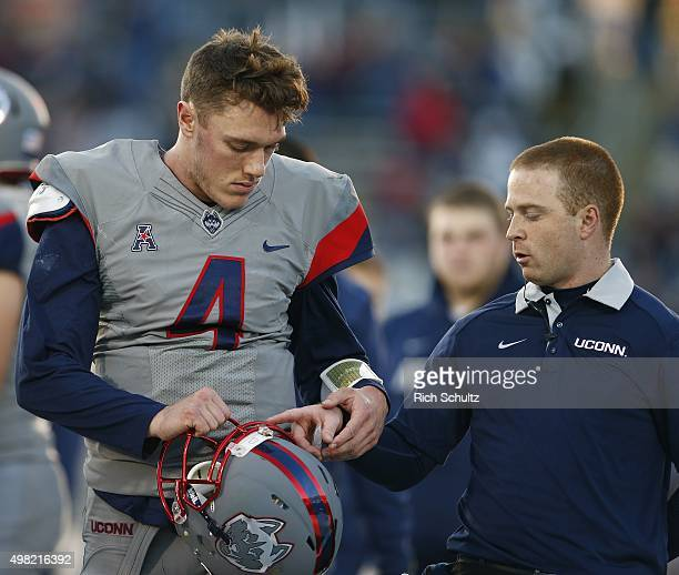 Quarterback Bryant Shirreffs of the Connecticut Huskies walks off the field with a member of the training staff during the first quarter against the...