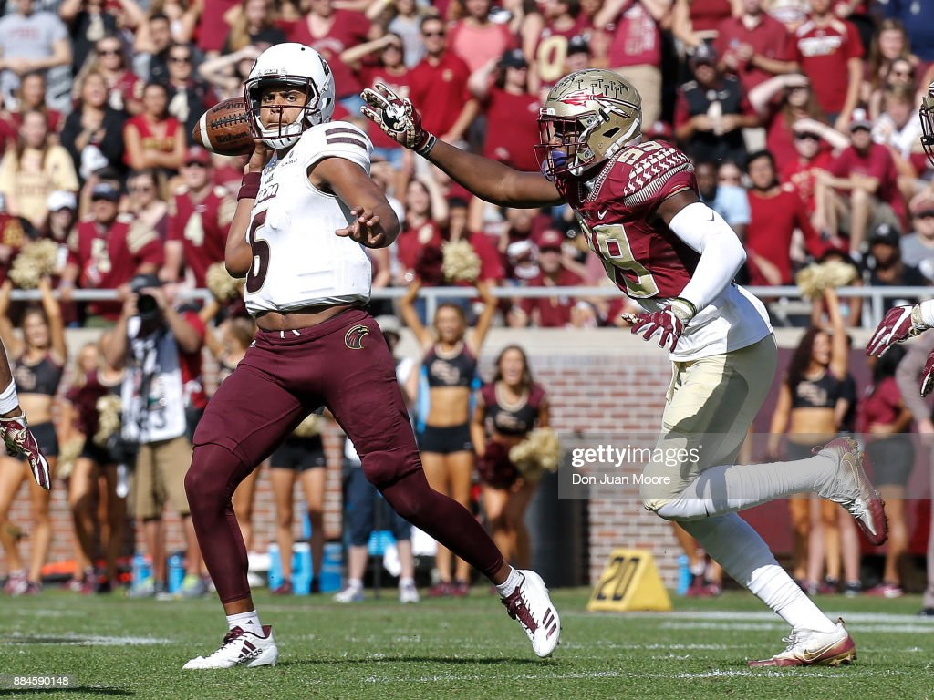 Quarterback Caleb Evans #6 of the Louisiana Monroe Warhawks avoids a tackle by Defensive End Brian Burns #99 of the Florida State Seminoles during the game at Doak Campbell Stadium on Bobby Bowden Field on December 2, 2017 in Tallahassee, Florida. Florida State defeated Louisiana Monroe 42 to 10.