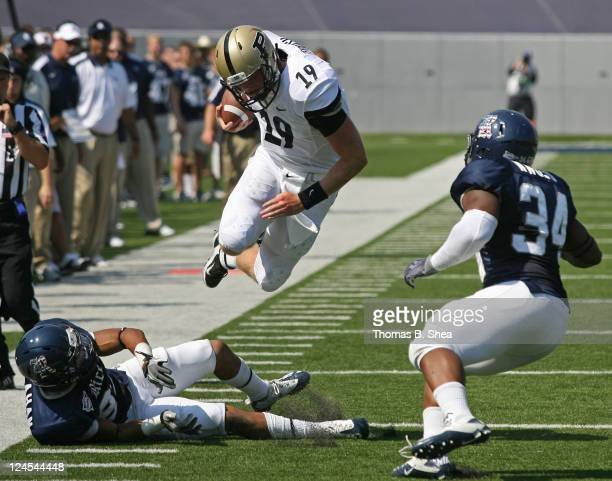 Quarterback Caleb TerBush of the Purdue Boilermakers is tripped up by defensive lineman Brian Stacey of the Rice Owls in the first half on September...