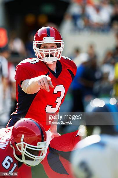 quarterback calling signals at line of scrimmage - quarterback stock pictures, royalty-free photos & images