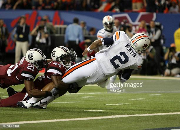 Quarterback Cam Newton of the Auburn Tigers dives in for a first quarter touchdown while safety DeVonte Holloman and linebacker Tony Straughter of...