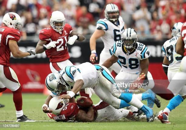 Quarterback Cam Newton of the Carolina Panthers lays a hit on linebacker Daryl Washington of the Arizona Cardinals after Washington intercepted a...