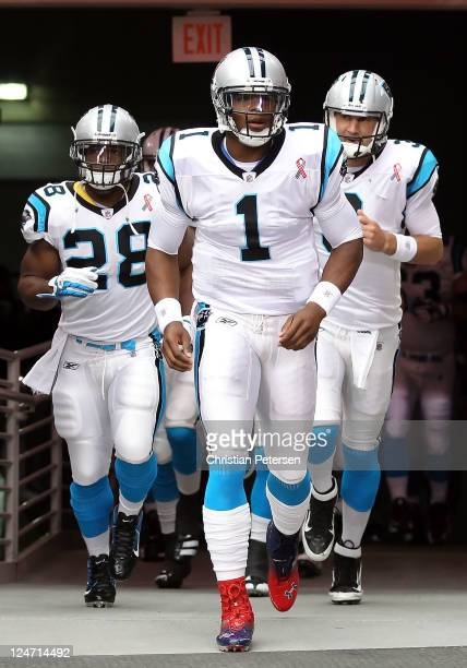 Quarterback Cam Newton of the Carolina Panthers leads teammates Jonathan Stewart and Derek Anderson out onto the field for warm ups to the NFL season...
