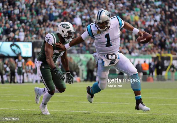 Quarterback Cam Newton of the Carolina Panthers runs the ball to score a touchdown against outside linebacker Bruce Carter of the New York Jets...