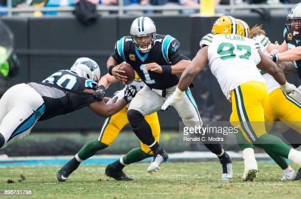 Quarterback Cam Newton of the Carolina Panthers scrambles against the Green Bay Packers during a NFL game at Bank of America Stadium on December 17...