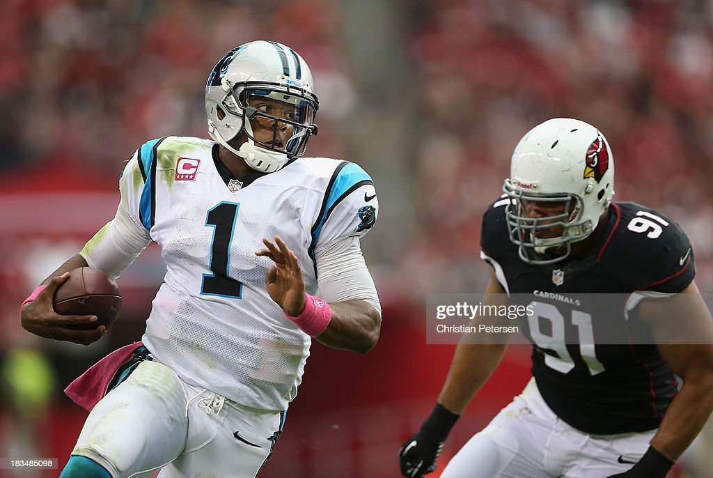Quarterback Cam Newton #1 of the Carolina Panthers scrambles with the football past defensive end Matt Shaughnessy #91 of the Arizona Cardinals during the NFL game at the University of Phoenix Stadium on October 6, 2013 in Glendale, Arizona. The Cardinals defeated the Panthers 22-6.