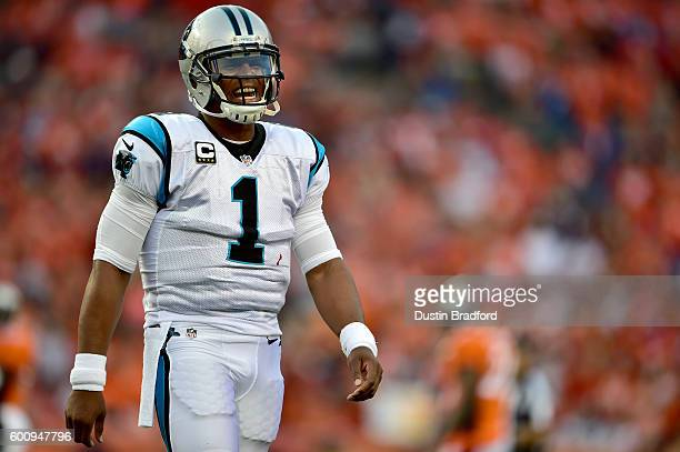Quarterback Cam Newton of the Carolina Panthers smiles in the first quarter against the Denver Broncos at Sports Authority Field at Mile High on...