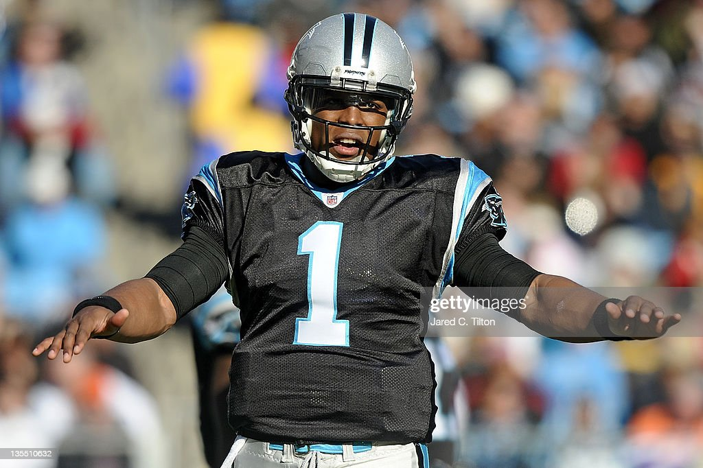 Quarterback Cam Newton #1 of the Carolina Panthers stretches his arms during the game against the Atlanta Falcons at Bank of America Stadium on December 11, 2011 in Charlotte, North Carolina.