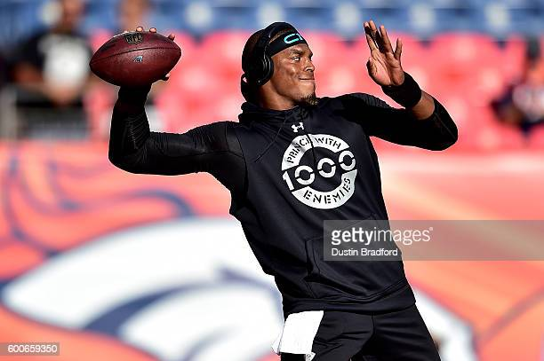 Quarterback Cam Newton of the Carolina Panthers warms up before taking on the Denver Broncos at Sports Authority Field at Mile High on September 8...