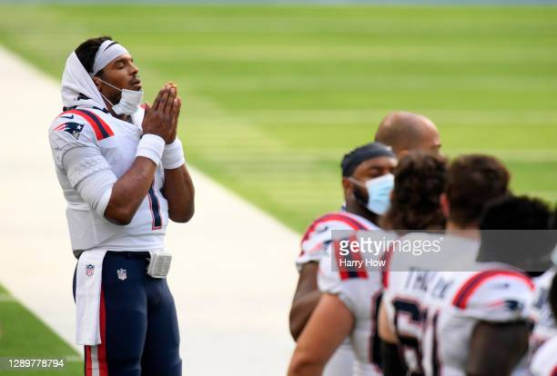 Quarterback Cam Newton of the New England Patriots on the side line during the playing of the National Anthem prior to the game against the Los...