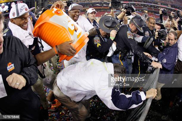 Quarterback Cameron Newton of the Auburn Tigers dumps gatorade on head coach Gene Chizik as they celebrate the Tigers 2219 victory with the fans...
