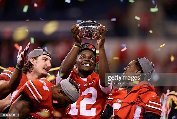 Quarterback Cardale Jones of the Ohio State Buckeyes lifts the Big Ten trophy after his team defeated the Wisconsin Badgers 59-0 in the Big Ten...