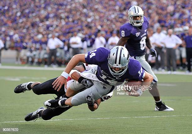 Quarterback Carson Coffman of the Kansas State Wildcats gets tackled from behind by linebacker Tyler Holmes of the Massachusetts Minutemen, just...