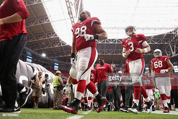 Quarterback Carson Palmer and defensive tackle Corey Peters of the Arizona Cardinals walk off the field prior to the start of the NFL game against...