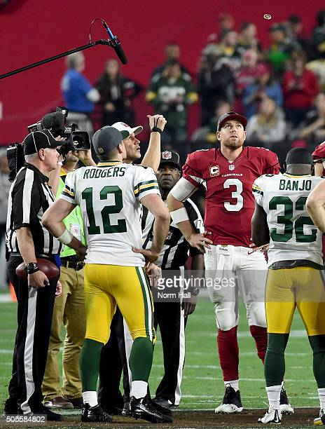 Quarterback Carson Palmer of the Arizona Cardinals and quarterback Aaron Rodgers of the Green Bay Packers watch the first of two overtime coin tosses...