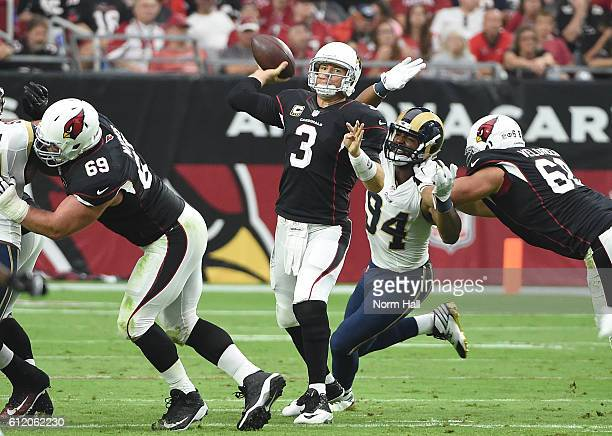 Quarterback Carson Palmer of the Arizona Cardinals looks to make a pass in front of defensive end Robert Quinn of the Los Angeles Rams during the...
