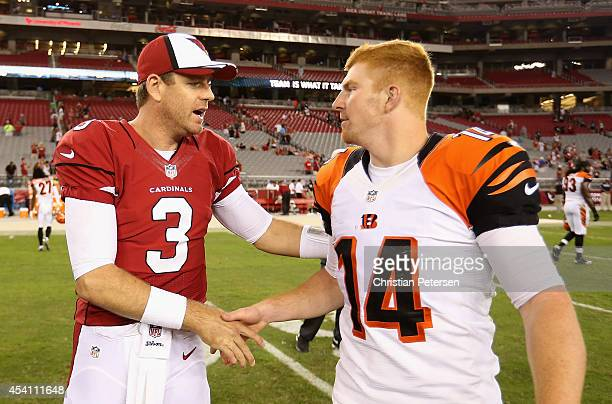 Quarterback Carson Palmer of the Arizona Cardinals talks with quarterback Andy Dalton of the Cincinnati Bengals following the preseason NFL game at...