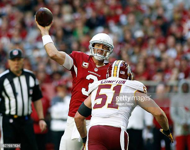 Quarterback Carson Palmer of the Arizona Cardinals throws a pass as he is pressured by Will Compton of the Washington Redskins during the first...