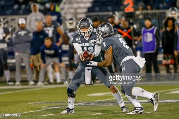 Quarterback Carson Strong of the Nevada Wolf Pack hands the ball off to running back Devonte Lee of the Nevada Wolf Pack during the game between the...