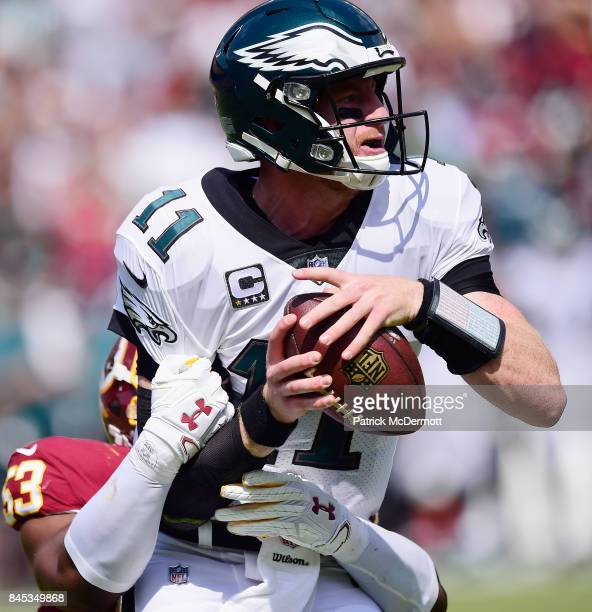 Quarterback Carson Wentz of he Philadelphia Eagles is taken down by Zach Brown of the Washington Redskins in the second quarter at FedExField on...