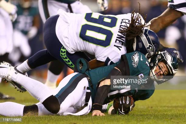 Quarterback Carson Wentz of the Philadelphia Eagles is hit by Jadeveon Clowney of the Seattle Seahawks during the NFC Wild Card Playoff game at...