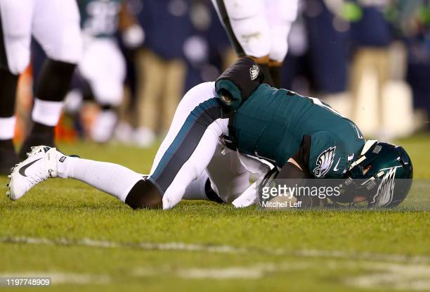Quarterback Carson Wentz of the Philadelphia Eagles is slow to rise after hit by Jadeveon Clowney of the Seattle Seahawks during the NFC Wild Card...