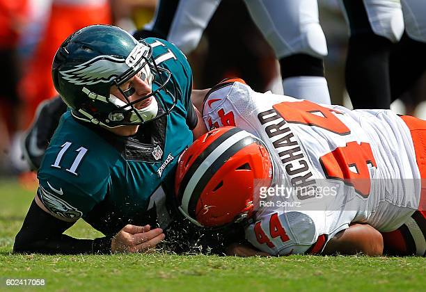 Quarterback Carson Wentz of the Philadelphia Eagles is tackled after making a pass by Nate Orchard of the Cleveland Browns during the second quarter...