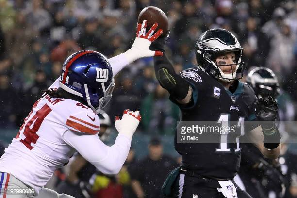 Quarterback Carson Wentz of the Philadelphia Eagles looks to pass over the defense of linebacker Markus Golden of the New York Giants during the game...