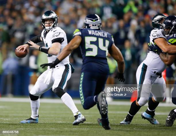 Quarterback Carson Wentz of the Philadelphia Eagles looks to pass under pressure from middle linebacker Bobby Wagner of the Seattle Seahawks in the...