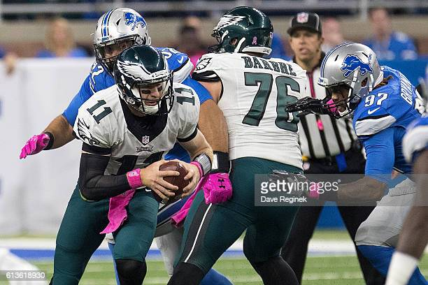 Quarterback Carson Wentz of the Philadelphia Eagles runs with the football past defensive end Armonty Bryant of the Detroit Lions during an NFL game...