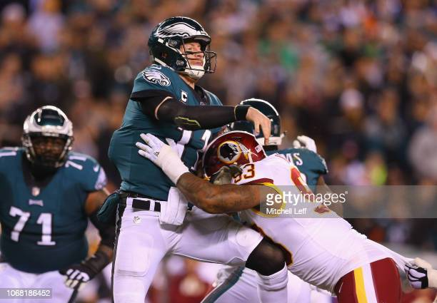 Quarterback Carson Wentz of the Philadelphia Eagles throws a pass as he is hit by defensive end Jonathan Allen of the Washington Redskins during the...