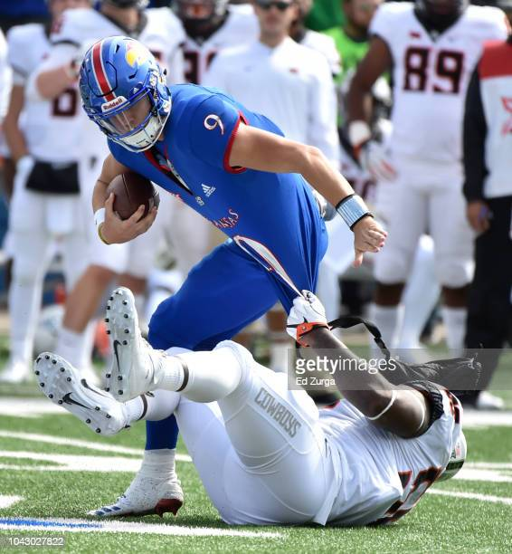 Quarterback Carter Stanley of the Kansas Jayhawks is tackled by Enoch Smith Jr. #56 of the Oklahoma State Cowboys in the second quarter at Memorial...