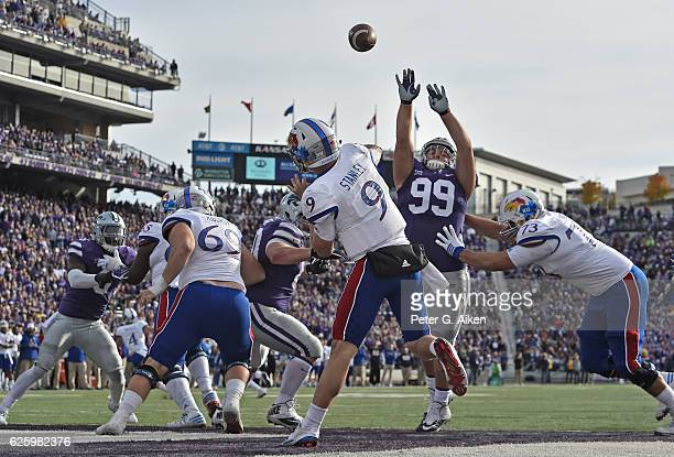 Quarterback Carter Stanley of the Kansas Jayhawks throws a pass from his own end zone against pressure from defensive tackle Trey Dishon of the...