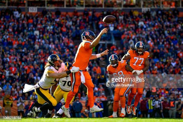 Quarterback Case Keenum of the Denver Broncos completes a pass after scrambling out of the pocket under pressure by nose tackle Javon Hargrave and...