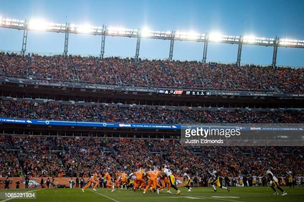 Quarterback Case Keenum of the Denver Broncos hands the ball to running back Phillip Lindsay in a general view during the third quarter of a game at...