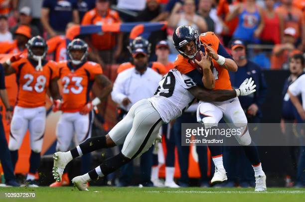 Quarterback Case Keenum of the Denver Broncos is hit by linebacker Tahir Whitehead of the Oakland Raiders in the fourth quarter of a game at Broncos...