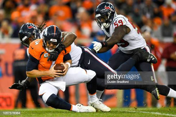 Quarterback Case Keenum of the Denver Broncos is sacked by outside linebacker Jadeveon Clowney of the Houston Texans in the fourth quarter of a game...