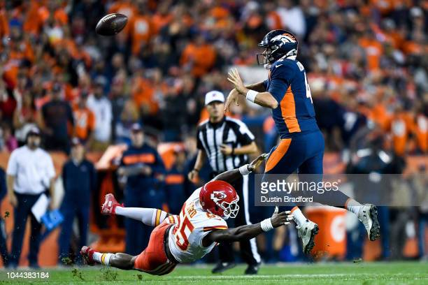 Quarterback Case Keenum of the Denver Broncos leaps and throws for a completion as linebacker Dee Ford of the Kansas City Chiefs attempts to tackle...