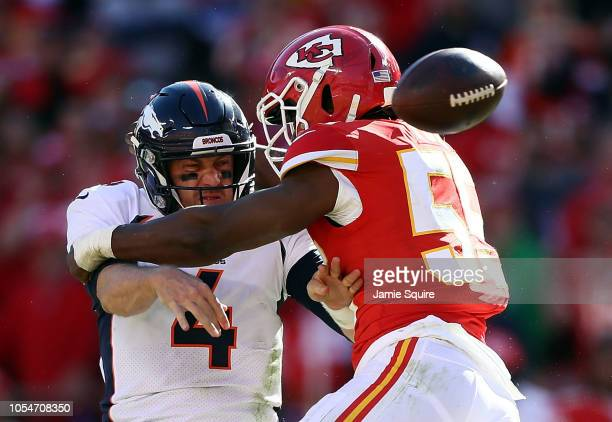 Quarterback Case Keenum of the Denver Broncos loses the ball as he is tackled by linebacker Reggie Ragland of the Kansas City Chiefs during the game...
