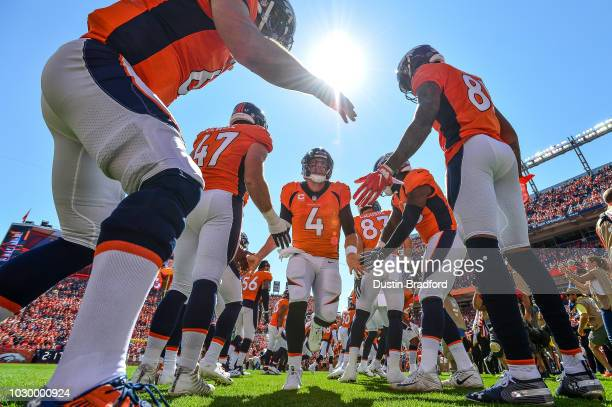 Quarterback Case Keenum of the Denver Broncos runs onto the field during player introductions before a game against the Seattle Seahawks at Broncos...