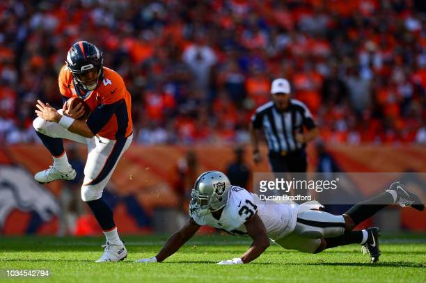 Quarterback Case Keenum of the Denver Broncos scrambles as defensive back Marcus Gilchrist of the Oakland Raiders defends in the fourth quarter of a...